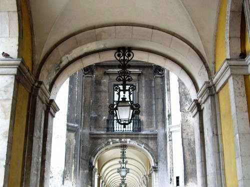 A rustic lantern hangs from a colonnade near the commercial center of Lisbon.