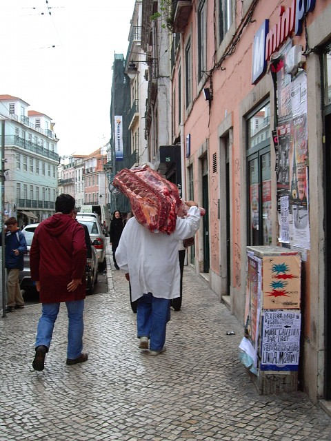 A butcher casually carries a large portion of a cow to his butcher shop.